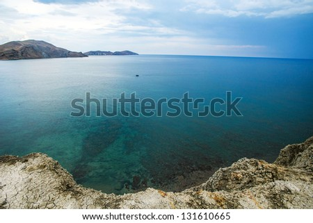 A landscape on sea. The yellow rock, azure water and cloudy sky.