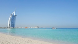 A landscape view of Dubai beach and sea in summer, famous building and fishing boats background. UAE.