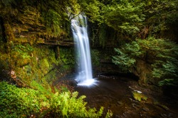 A landscape view of Glencar waterfall outside of Sligo, Ireland with green foliage
