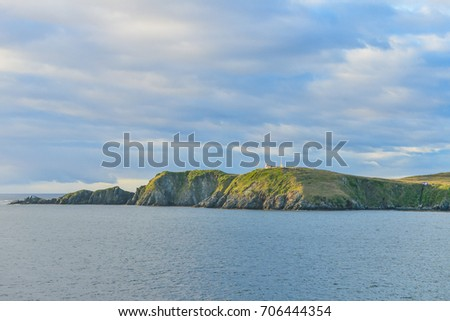 A Landscape view of the  Cape Horn headland, showing the Lighthouse. Taken from a passing Cruise ship, on route to Antarctica.