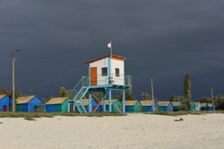 A landscape with a sandy beach. A construction with a lifeguard tower and a row of wooden colorful one-story cabins for vacationers against a dark blue, pre-thunderstorm sky.Nobody. Resting on the sea