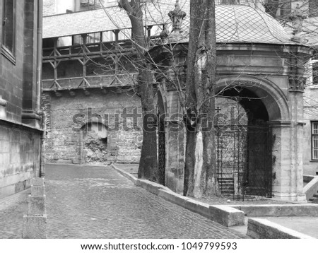 A lane in the ancient city near the church. Black and white. An ancient wall on the background.