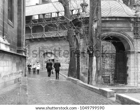 A lane in the ancient city near the church. People on the street. Black and white.
