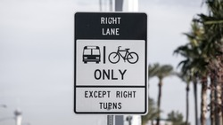 A lane restriction traffic sign indicating right lane is designated for bus and bicycles except when making right turns. Found on W. Sahara Avenue in Las Vegas, Nevada, USA.
