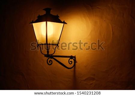 A lantern on the wall illuminates at night.