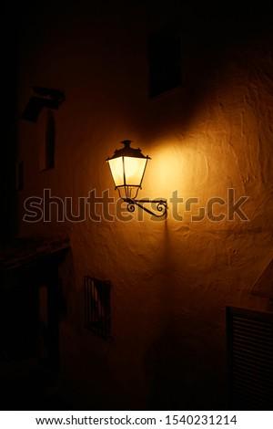 A lantern on the wall illuminates at night.  #1540231214