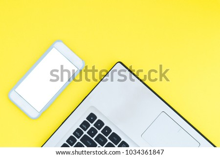 A laptop and a smartphone with a white screen on a yellow background. Minimalistic working space with a place for text. Flat Layout Layout. #1034361847