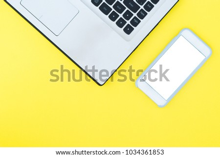 A laptop and a smartphone with a white screen on a yellow background. Minimalistic working space with a place for text. Flat Layout Layout. #1034361853