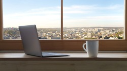 A laptop and cup of coffee on window sill with view on city