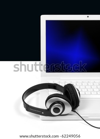 A laptop computer with a set of headphones isolated against a white background