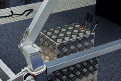 A large aluminium boat bow control box with three levers, a sunroof hinge assembly with clear welding seams and a grey carpet and part of a single dark rope at background