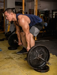 A large and muscular asian man does block deadlifts. Barbell elevated from floor with steel plates. Working out at a hardcore gym.