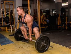 A large and muscular asian man does sumo barbell deadlifts at a hardcore gym. Working out quadriceps, glutes, hamstrings, and other muscles of the posterior chain.