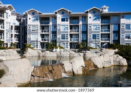 A large apartment building with pond and fountain. - stock photo