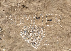 A large, beautiful heart made of sea shells laid out on sea sand with the inscription and letters Summer. Photography, concept, top view.