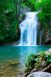 A large beautiful waterfall in a forest with blue water and a trees.