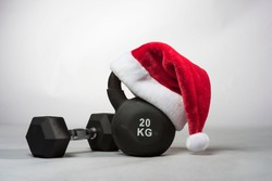 A large black Kettlebell wearing a red  Santa hat with a dumbbell next to it on a plain light gray background
