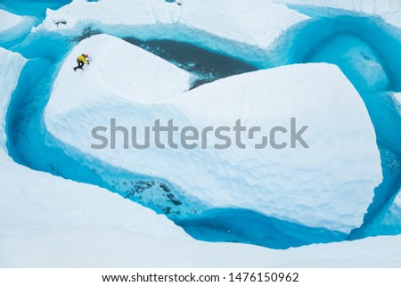 A large blue lake on the Matanuska Glacier in Alaska fills in many narrow canyons cut from the ice by water the previous summer. Over winter, the drains freeze and a lake fills the canyons. #1476150962