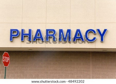 A large blue pharmacy sign on the outside of a building. - stock photo