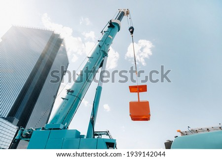 A large blue truck crane stands ready for operation on a site near a large modern building. The largest truck crane with a yellow cradle for solving complex tasks. Foto stock ©