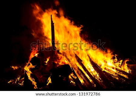 A large bonfire made of logs and timber is raging.