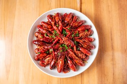 A large bowl of delicious braised crayfish on a wooden table