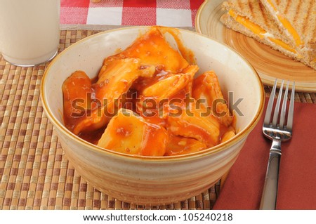 A large bowl of ravioli with tomato sauce