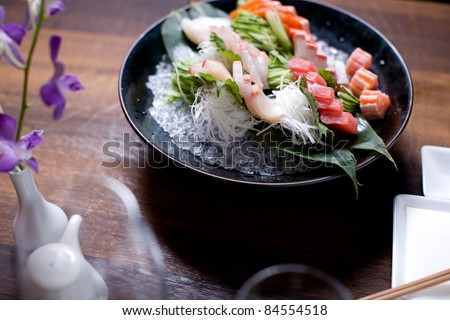 A large bowl of sashimi in a dinner setting