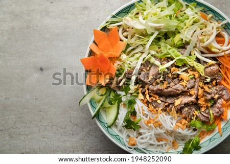 A large bowl of traditional South Vietnamese noodle dish called Bun Bo Nam Bo with beef, noodles, fresh herbs, pickled vegetables and fish sauce. Stok fotoğraf ©