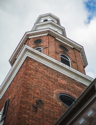 A large brick church tower of an old colonial church in Downtown Alexandria, VA.