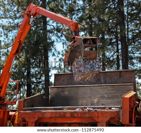 A large brick of crushed aluminum cans is lifted by a orange crane out of a compacting machine.