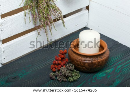 A large candle in a clay vessel. Bunches of fragrant herbs hang nearby. A bunch of mountain ash lies. It stands on painted boards painted in black and green.