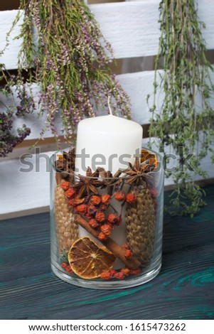 A large candle in a glass vessel. Cones, mountain ash, anise stars, cinnamon sticks are poured into it for decoration. Bunches of fragrant herbs hang nearby. It stands on painted boards