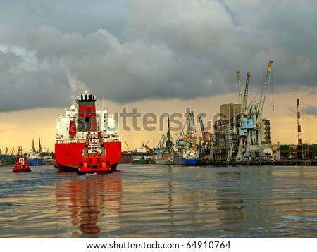 A large cargo ship enters the port escorted by tugboats. Gdansk, Poland.
