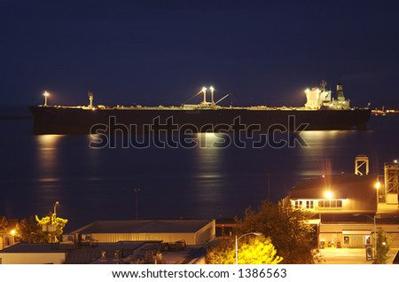 A large cargo ship pulls into port as a warm summer night sets in on a small coastal city.