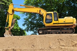 A large caterpillar backhoe parked on the hill of dirt it has dug.