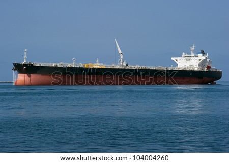 A large chemical tanker ship prepares to leave a harbor