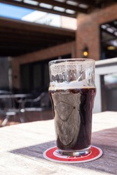 A large clear beer glass of dark ale sits on a table in a micro brewery patio. The beer has froth on the top part of the glass.  The patio has large glass windows, door and pillars. The roof is open.