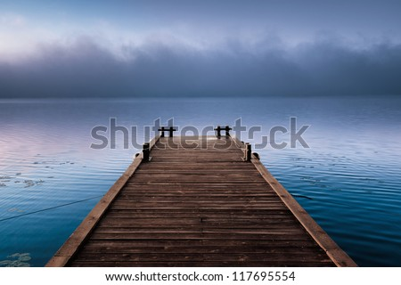 A large cloud of misty an empty dock in morning calm wind