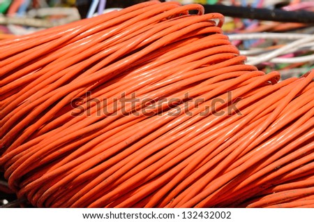 A large coil of copper electrical wire sits in a bin awaiting recycling at a metal recycling scrap yard