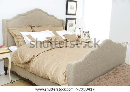 A Large Comfortable Bedroom With A Bed And Lots Of Pillows