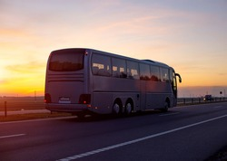A large comfortable passenger bus against the orange sky with sunset rides on the highway. The concept of European passenger transportation in companies, e-ticket
