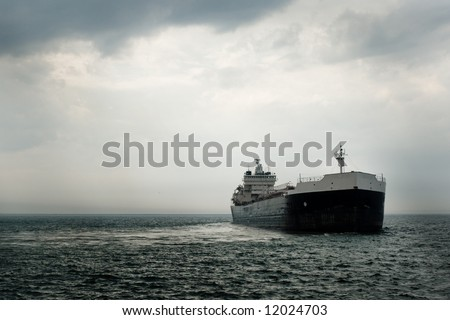 A large commercial vessel departs from harbor after a storm.