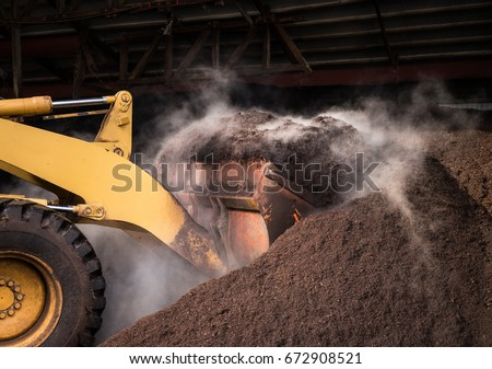 A large compost pile being churned by a bulldozer.