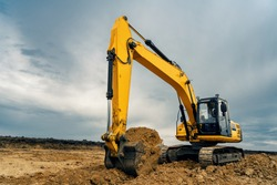 A large construction excavator of yellow color on the construction site in a quarry for quarrying. Industrial image.