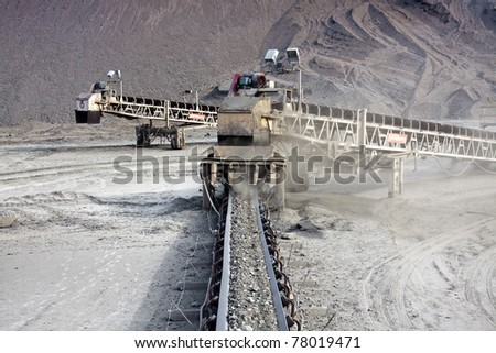 a large conveyor belt carrying golden ore