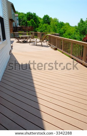 A large deck on the outside of the back of a residential house.