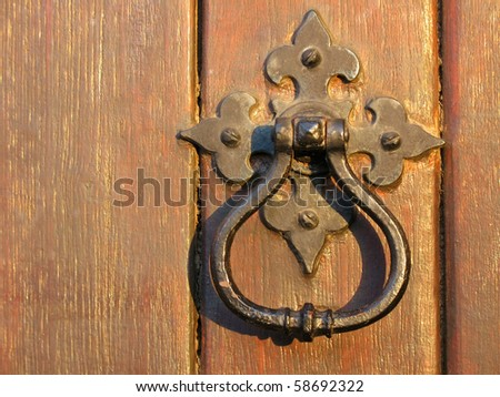 A large decorative vintage door handle on a wooden door