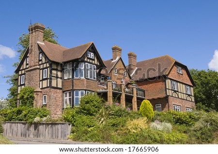 Large detached tudor style house with a blue sky stock photo