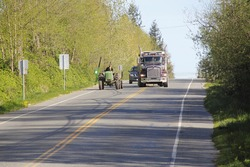 A large dump truck passes a farm tractor on a two lane road/Farm Vehicles and Road Traffic/A truck passes a farm tractor.
